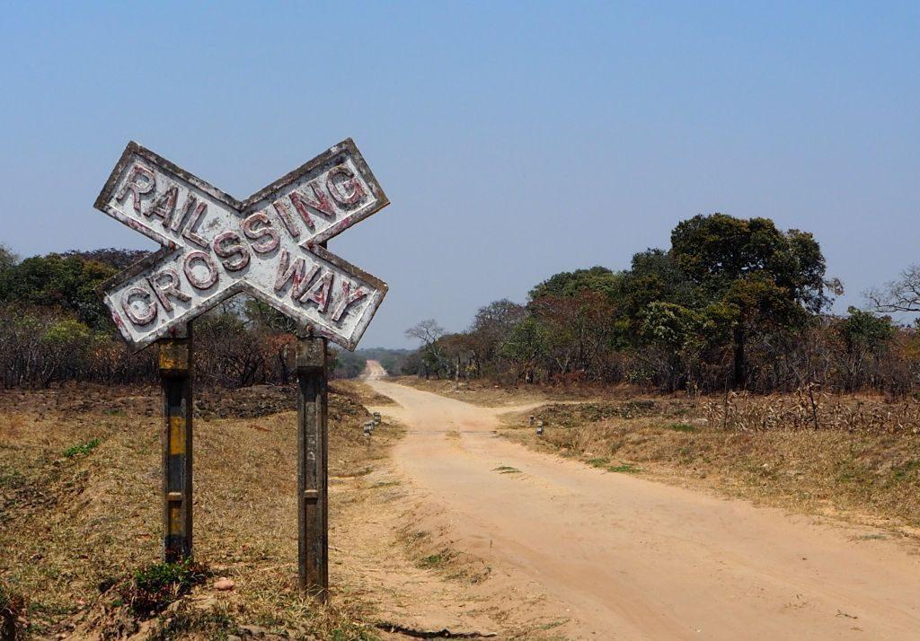 endlose Strasse, Schild mit Rail way crossing  auf linker Seite